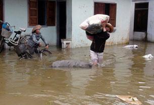 Người dân di chuyển đồ đạc do lũ tràn về tại Qui Nhơn, Bình Định hôm 16/11/2013.
