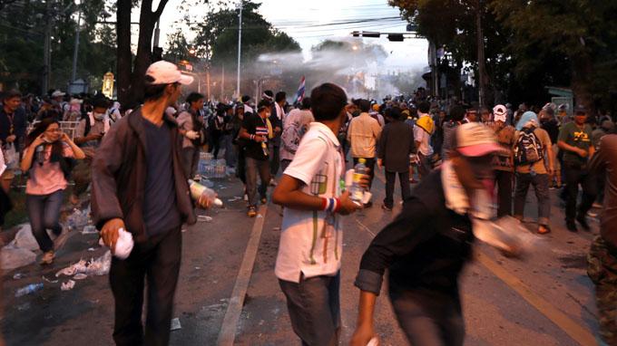 Người biểu tình bỏ chạy khi cảnh sát bắn hơi cay, xịt vòi rồng ở gần phủ thủ tướng Thái Lan - Ảnh: V.Phương