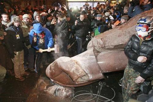 Đám đông quá khích dùng rìu đập phá tượng Lenin sau khi đã giật ngã bức tượng cao hơn 3 m này bằng dây thừng - Ảnh: Reuters