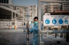 Một nhân viên bảo vệ đóng cửa chợ gia cầm tại Hồng Kông hôm 28 tháng Một. Một sự bùng nổ số người nhiễm cúm gia cầm tại Trung Quốc, với một chủng virus mới đã tái xuất hiện (PHILIPPE LOPEZ/AFP/Getty Images)