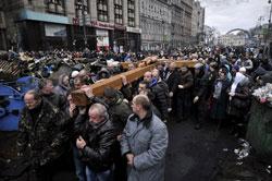Người dân Ukraine mang một cây thánh giá lớn tưởng niệm cho các nạn nhân của cuộc xung đột gần đây giữa người biểu tình và cảnh sát tại Kiev. Ảnh chụp hôm 24/2/2014. AFP photo