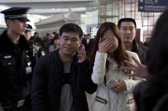 Một người phụ nữ rơi nước mắt tại sảnh chờ của Sân Bay Quốc tế Bắc Kinh, Trung Quốc, hôm thứ 7, sau khi rộ lên tin tức liên quan đến chiếc máy bay Boeing của hãng hàng không Malaysia Airlines Mất tích trong hành trình từ Kualar Lumpur đến Bắc Kinh. (AP Photo/Ng Han Guan)