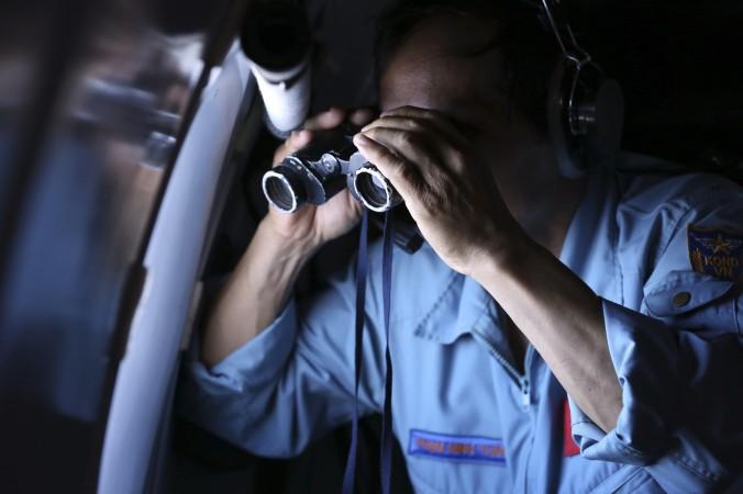 (Ảnh: Đại tá không quân Việt Nam, Phạm Minh Tuấn, dùng ống nhòm trên máy bay trong nhiệm vụ tìm kiếm máy bay MH370 của Hàng không Malaysia bị mất tích tại Vịnh Thái Lan, thứ 5, ngày 13 tháng Ba 2014. Không có cuộc gọi báo nguy cấp, không dấu hiệu mảnh vụn, và rất ít câu trả lời, sự biến mất của máy bay hàng không Malaysia đang trở thành một trong những bí ẩn lớn nhất của ngành hàng không, kể từ khi Amelia Earhart biến mất trên Thái Bình Dương vào năm 1937. (Ảnh AP)