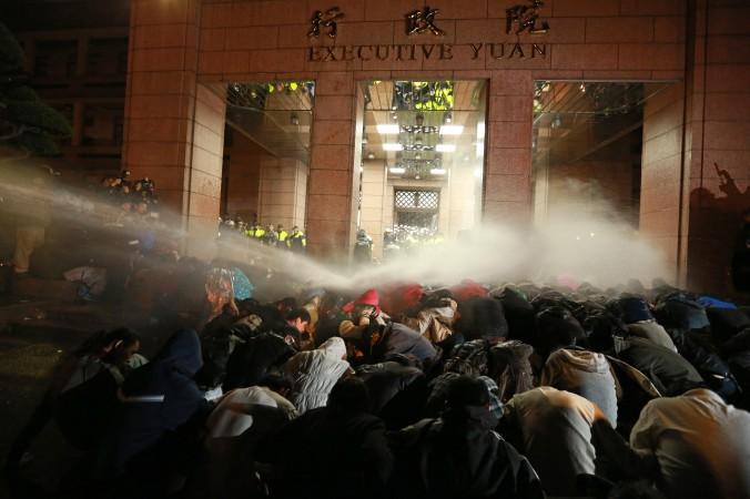Vòi rồng phun vào nhữn người biểu tình ở bên ngoài Viện Hành Chính, thủ đô Đài Bắc vào sáng sớm ngày 24 tháng Ba năm 2014. Các cuộc biểu tình xảy ra sau khi tổng thống Mã Anh Cửu ký kết một thỏa thuận thương mại đầy tranh cãi với Hoa lục (Ảnh STR/AFP/Getty)
