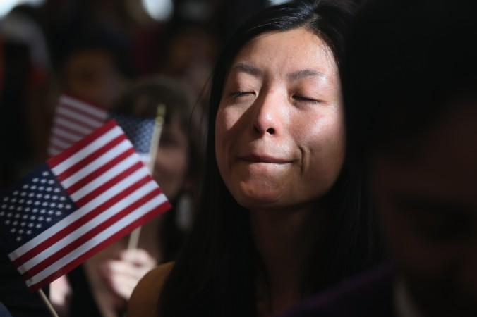 Người Trung Quốc nhập cư, đang làm việc ở Quỹ Phòng hộ, Yi Shu kìm những dòng nước mắt khi tuyên thệ công dân ở lễ nhập tịch tại New York, ngày 9 tháng 4 năm 2013 (John Moore/ Getty Images)
