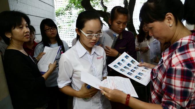 Thí sinh dự thi vào trường ĐH Kinh Tế TP.HCM làm thủ tục trước giờ thi môn toán tại điểm thi trường THPT Bùi Thị Xuân Q.1, TP.HCM - Ảnh: Như Hùng