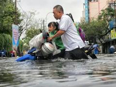 Nước ngập gần đến yên xe khiến phụ huynh vất vả đón con.  Photo: Minh Quan/tinmoitruong