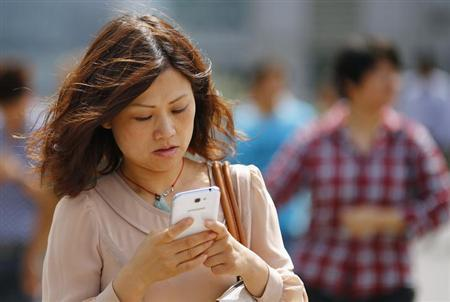 A woman looks at her smartphone as she walks on a busy street in downtown Shanghai, September 25, 2013.