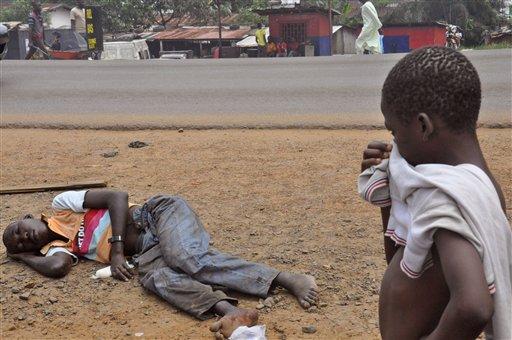 Một đứa trẻ đang bịt mũi đứng nhìn người đàn ông nghi nhiễm virus Ebola đang nằm vạ vật tại một phố chính của khu đông dân cư ở Monrovia, Liberia vào thứ 6 ngày 12 tháng 9 năm 2014. (Ảnh Abbas Dulled)