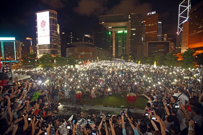 """Vào ngày 31/8/2014, một cuộc mit tinh biểu tình diễn ra tại công viên Tamar bên ngoài Văn phòng Chính phủ Trung ương Hồng Kông nhằm phản đối quyết định thắt chặt dân chủ ở Hong Kong của Bắc Kinh. Những người biểu tình giơ cao điện thoại di động tượng trưng cho những ngọn nến như một lời cam kết cho phong trào """"bất tuân dân sự"""". (Poon/Epoch Times)"""