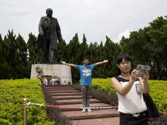 Khách du lịch chụp hình kỷ niệm trước tượng Đặng Tiểu Bình tại Thâm Quyến, Quảng Đông. Ảnh chụp ngày 19/08/2014. REUTERS/Tyrone Siu