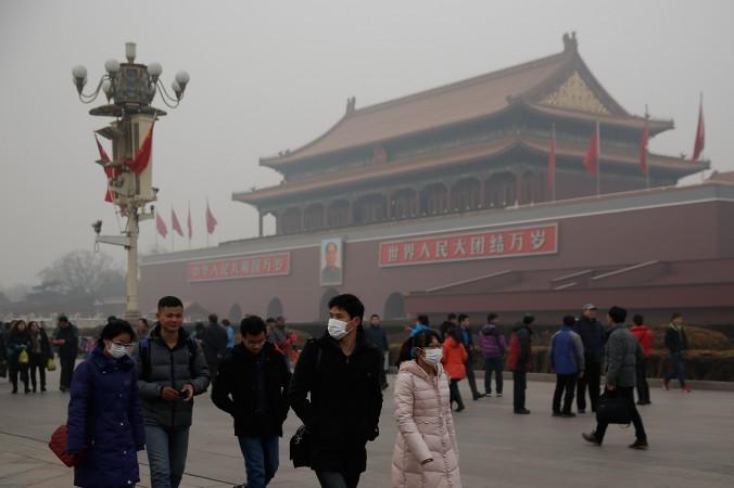 Du khách Trung Quốc đeo khẩu trang trên Quảng trường Thiên An Môn trong khoảng thời gian ô nhiễm nặng nề vào ngày 25/4/2014 ở Bắc Kinh, Trung Quốc. Các nhà lãnh đạo hàng đầu Trung Quốc sẽ tập trung lại trong phiên họp toàn thể lần thứ 4 Ban Chấp hành Trung ương Đảng Cộng Sản Trung Quốc lần thứ 18 từ ngày 20/10 đến ngày 23/10/2014. (Lintao Zhang/Getty Images)