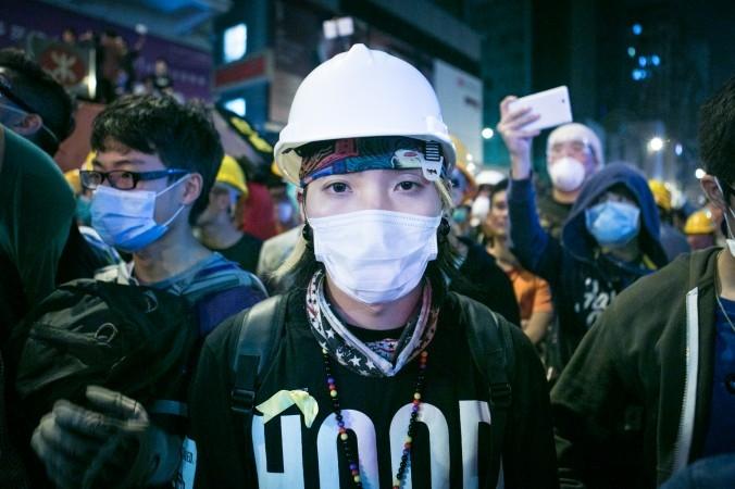 Một người biểu tình đeo khẩu trang bảo vệ đứng ở hàng đầu đối mặt với cảnh sát tại Mong Kok, Hồng Kông, ngày 5/11/2014. (Ảnh: Benjamin Chasteen/ Báo Đại Kỷ Nguyên)