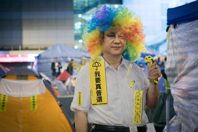 Bộ tóc giả đội trên bức hình của ông Tập Cận Bình trong lễ hội Halloween tổ chức ở quận Trung Tâm, Hồng Kông ngày 3/11/2014. Người biểu tình đã sử dụng hình ảnh Tập Cận Bình như một lá chắn — cảnh sát sẽ không dám tháo dỡ nó bởi họ sợ việc làm này sẽ bị ghi hình và sử dụng để chống lại bản thân họ. (Ảnh Benjamin Chasteen/ Báo Đại Kỷ Nguyên)