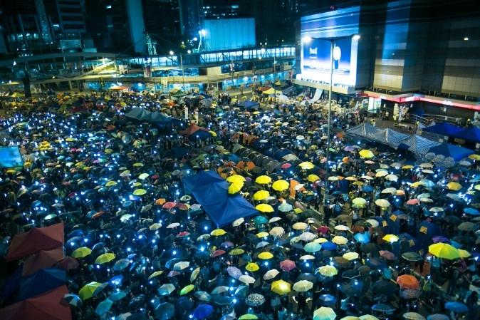 Hàng ngàn người đã giương ô và vẫy điện thoại tại Admiralty, Hồng Kông, ngày 28/10/2014, yêu cầu một chế độ dân chủ hơn. Hiện chưa thể thấy được kết cục nào rõ ràng cho chiến dịch đã kéo dài hơn một tháng nay. (Ảnh Benjamin Chasteen/ Báo Đại Kỷ Nguyên)