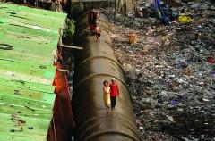 Nước ở Mumbai, Ấn Độ rất đắt đỏ, nhiều cư dân khu ổ chuột đã tận dụng những chỗ rò rỉ được tìm thấy hoặc tự mình tạo ra trên những đường ống lớn dẫn nước đến khu dân cư giàu có. Người nghèo của thành phố tránh rác thải của con người và xung quanh ngôi nhà bằng cách đi bộ trên các đường ống này.