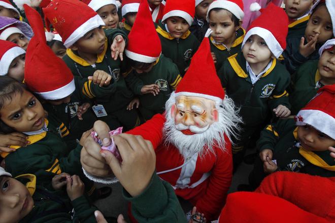 Một học sinh trong bộ đồ ông già Noel phân phát kẹo cho trẻ em ở thành phố Chandigarh, Ấn Độ.