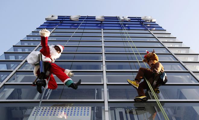 Các nhân viên lau dọn ăn vận đồ của ông già Noel và tuần lộc chào đón Giáng sinh tại một trung tâm mua sắm ở Tokyo, Nhật Bản.