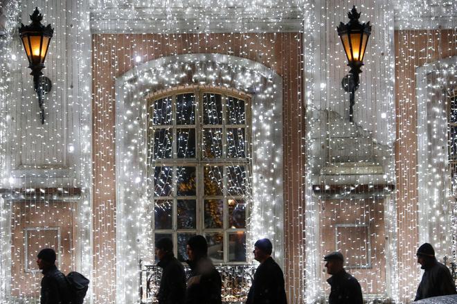 Người dân đi qua một tòa nhà được trang hoàng ở trung tâm Moscow, Nga.