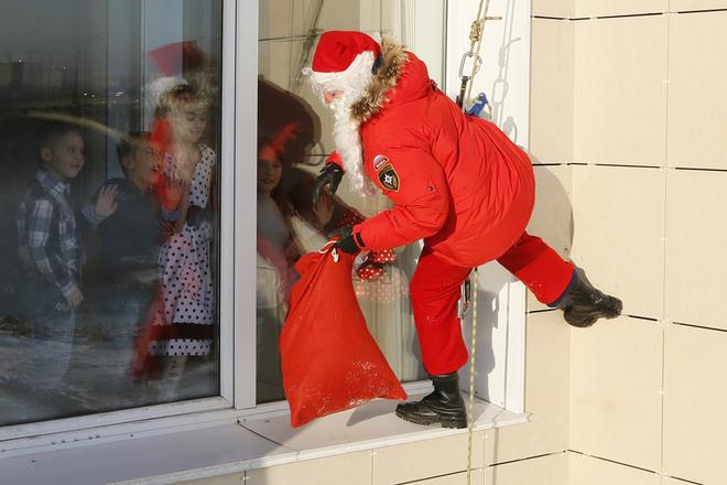 Alexei Trifonov, một thành viên của tổ chức dịch vụ Người giải cứu, mặc đồ ông già Noel, chuẩn bị phát quà cho nhân viên của Bộ Khẩn cấp Nga và con em của họ.