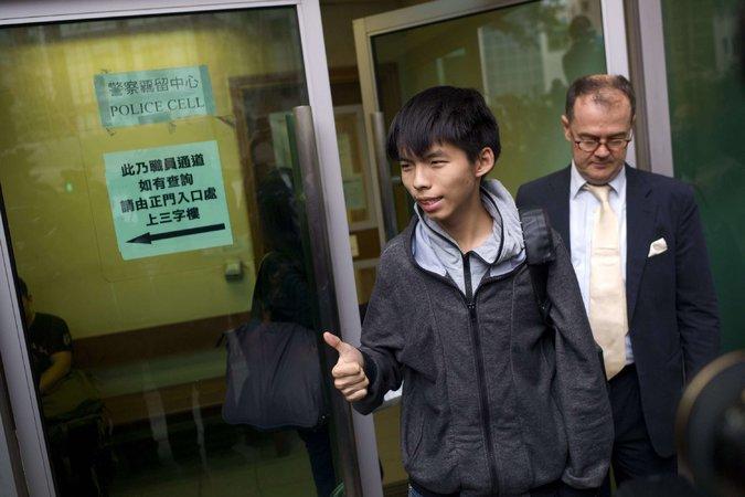 Thủ lĩnh phong trào biểu tình sinh viên ở Hồng Kông, Joshua Wong (Hoàng Chi Phong), đứng giữa, cùng luật sư bước ra khỏi tòa án ở Hồng Kông, ngày 27/11/2014. Wong và những người biểu tình dân chủ khác bị bắt giữ trong đợt trấn áp của cảnh sát nhằm dẹp bỏ những chướng ngại vật của người biểu tình tại quận Mong Kok. Wong được tại ngoại và vụ xét xử được hoãn lại đến ngày 14/1. (Ảnh Internet)