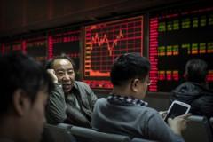 Những người giao dịch chứng khoán Trung Quốc trò chuyện trước bảng hiển thị các mã chứng khoán tại một công ty môi giới chứng khoán ở Bắc Kinh, Trung Quốc, ngày 22/1/2015. (Kevin Frayer / Getty Images)