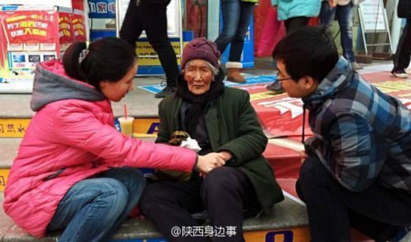 Cô gái nắm tay sưởi ấm cho bà lão ăn mày trên phố