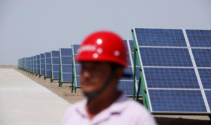 Một công nhân Trung Quốc đi bộ trong các mô-đun pin mặt trời của một dự án năng lượng quang điện kết nối với lưới điện có công suất 100MW mới được lắp đặt, vào ngày 21/7/2010 ở Đôn Hoàng, tỉnh Cam Túc phía Tây Bắc Trung Quốc. (Ảnh: Feng Li/Getty Images).