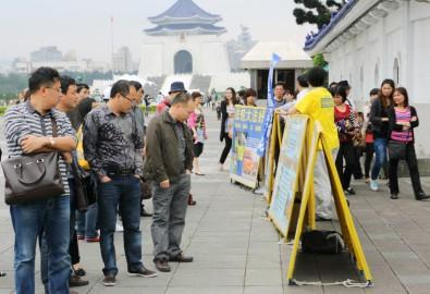 Du khách Trung Quốc dừng lại và chăm chú xem những thông tin về Pháp Luân Công