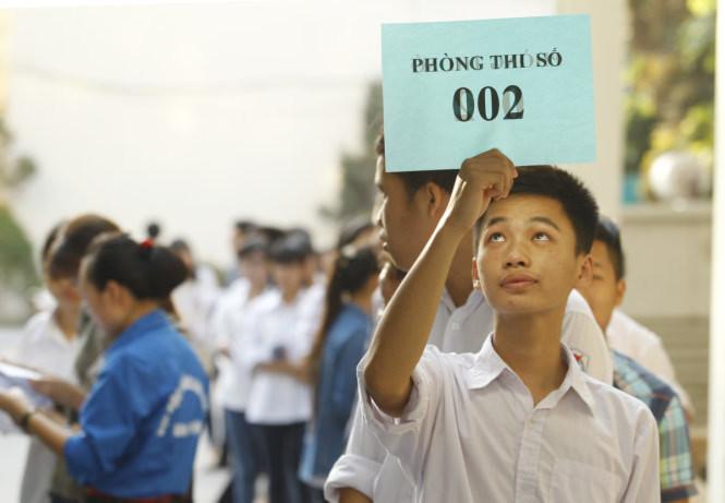 Một thí sinh cầm trên tay bảng hiệu của phòng thi tại nơi tập trung các thí sinh - Ảnh: Nguyễn Khánh