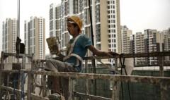 Một công nhân xây dựng Trung Quốc ngáp khi đang quét sơn phía bên ngoài của một khu phức hợp căn hộ mới ngày 29/8/2014 ở Bắc Kinh, Trung Quốc. Việc xây dựng nhanh chóng và đầu tư tràn lan vào bất động sản ở Trung Quốc đã tạo ra một bong bóng, và bong bóng này đang dần dần xì hơi. (Ảnh: Kevin Frayer/Getty Images)