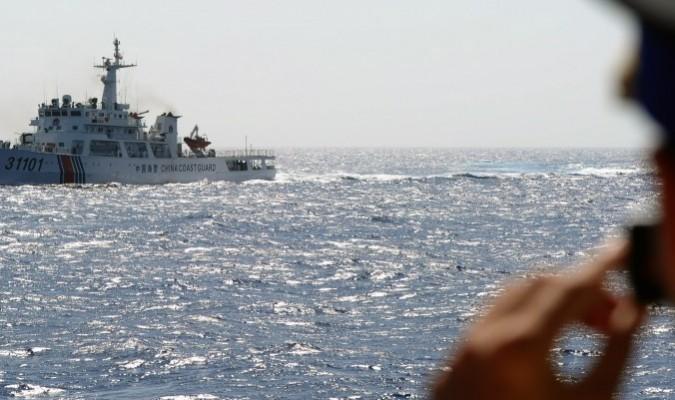 Một nhân viên bảo vệ bờ biển Việt Nam chụp ảnh một con tàu của Lực lượng bảo vệ bờ biển Trung Quốc trên Biển Đông vào ngày 14/5/2014, ngoài khơi bờ biển miền Trung Việt Nam. Chính quyền Trung Quốc hiện đang bảo vệ không phận trên khu vực này. (Ảnh: Hoàng Đình Nam/AFP/Getty Images)