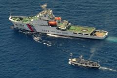 Một chiếc chiến thuyền Bảo vệ Bờ biển của Trung Quốc (phía trên) và một chiếc thuyền cung ứng của Philippines rơi vào tình trạng giằng co vì tàu Philippines muốn tiến đến Bãi Cỏ Mây (Second Thomas Shoal), một rạn san hô xa xôi ở Biển Đông được cả hai nước tuyên bố chủ quyền, ngày 29 tháng 3 năm 2014 ( Jay Directo/AFP/Getty Images)
