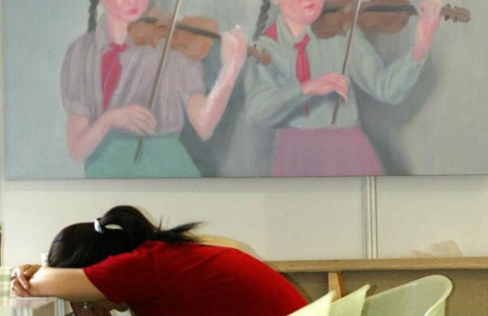Một người phụ nữ tranh thủ ngủ gục trên bàn ngay cạnh một bức tranh sơn dầu vẽ hai đoàn viên thanh niên chơi violin tại Phòng trưng bày Nghệ thuật Mùa xuân Thượng Hải, ngày 3/6/2004. (LIU JIN/AFP/Getty Images)