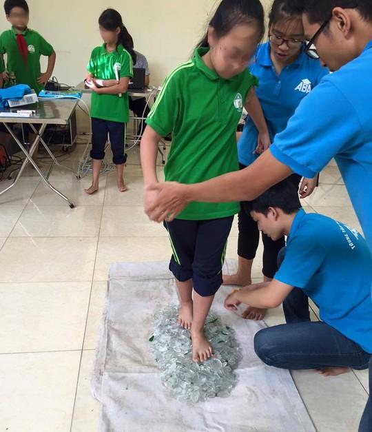 Học sinh thực hành đi trên thủy tinh vỡ tại Trung tâm giáo dục ABA. (Ảnh: nld.com.vn)