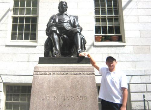 Hoàng Minh Tuệ bên tượng đài John Harvard tại Đại học Harvard (bang Massachusetts, Mỹ) trong chuyến du học bổng ASSIST năm 2013