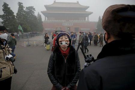 Một người đeo khẩu trang bảo vệ khỏi khói bụi dày đặc khi đứng cạnh viên cảnh sát cũng đeo khẩu trang tại Thiên An môn. Ô nhiễm không khí trầm trọng tiếp tục che phủ Bắc Kinh gần tuần qua bằng tầng tầng lớp lớp khói xám xịt dù chính quyền đã lệnh đóng cửa toàn bộ xa lộ và dừng hết các dự án xây dựng.
