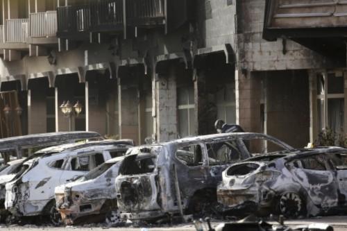 Cảnh sát xem xét những chiếc xe cháy bên ngoài khách sạn Spledid ở Burkina Faso, nơi phiến quân chiếm đóng trước khi bị tiêu diệt. Ảnh: Reuters