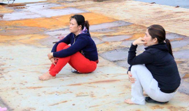 Chị Võ Thị Cảnh (vợ của ngư dân Huỳnh Văn Thạch trên tàu QNg 98495) cùng vợ của một ngư dân khác ngồi đợi tàu cập cảng - Ảnh: Trường Trung