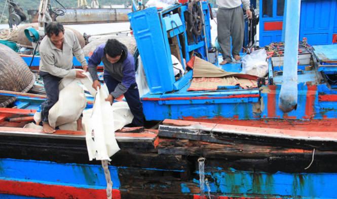 Ngư dân giúp nhau thu dọn ngư lưới cụ trên tàu bị nạn - Ảnh: Trường Trung