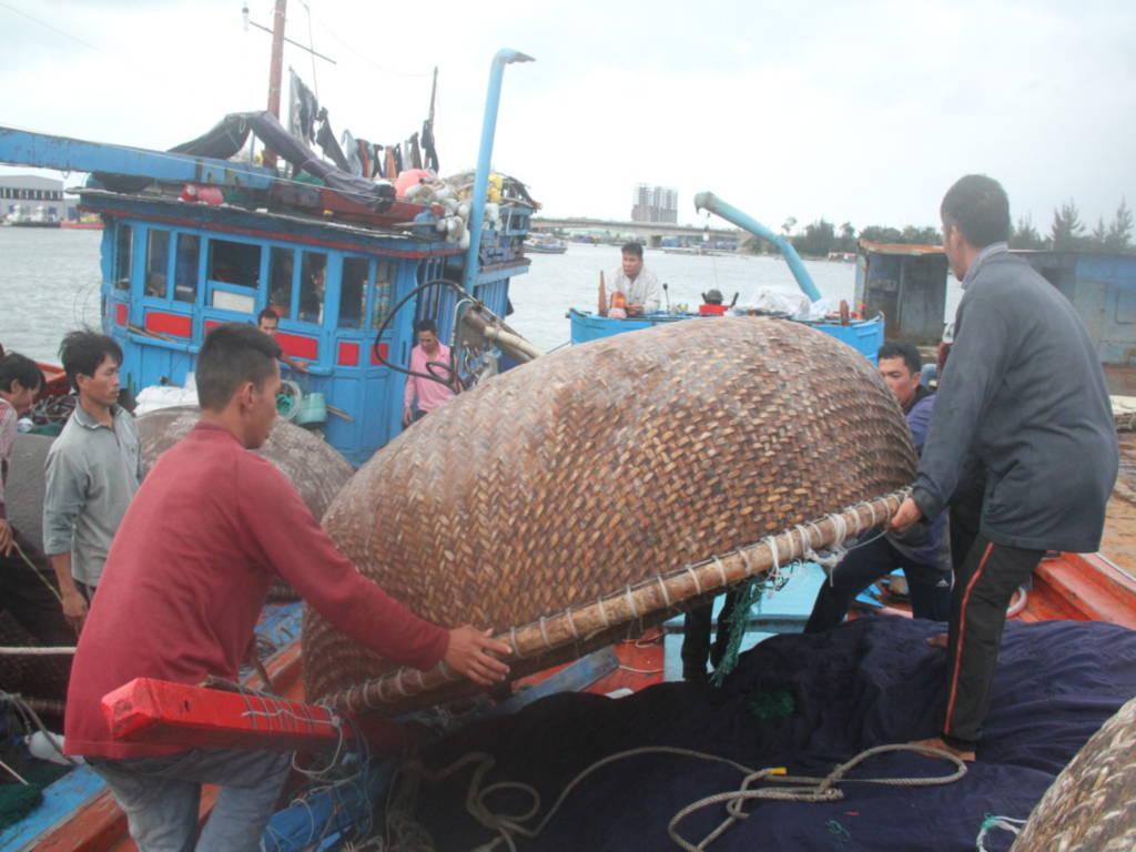 Các ngư dân trên tàu cá của ông Huỳnh Bi giúp dọn dẹp tàu cá bị nạn - Ảnh: Đoàn Cường