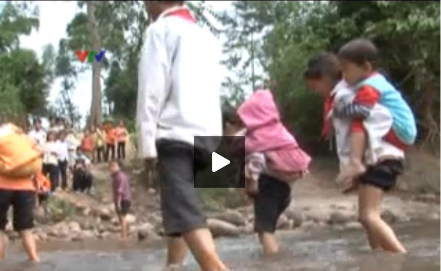 Cõng em lội suối đi học. Ảnh lấy từ video VTV