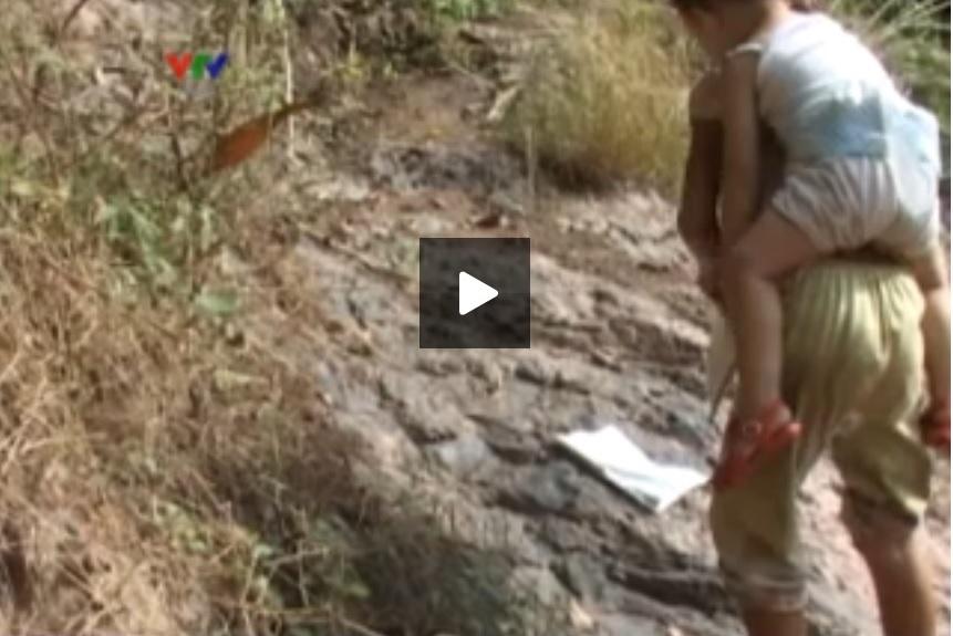 Sau khi lội suối, học sinh phải tiếp tục băng rừng cõng em đến trường. Ảnh cắt từ video VTV