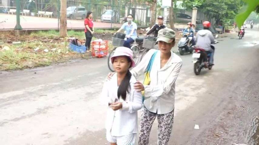 Bé Trúc Vy mới 9 tuổi dẫn theo người mẹ mù lòa cùng đi bán vé số