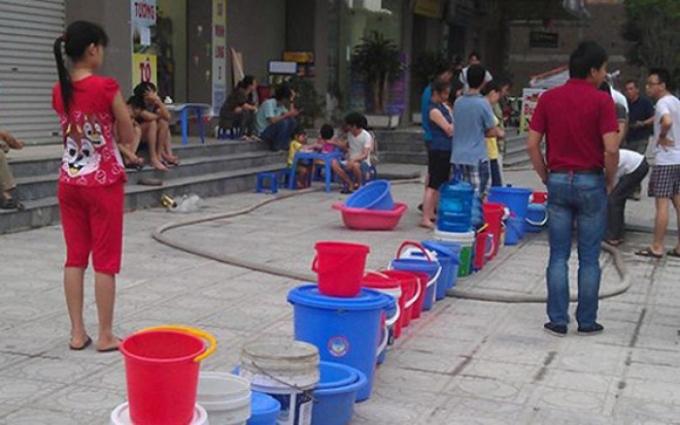 """Cảnh người dân Hà Nội huy động xô chậu xếp hàng chờ nước """"phân phối"""" vào mùa hè bao giờ mới kết thúc? Ảnh: Lao Động Thủ Đô"""