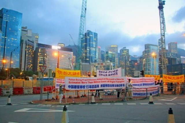 Các học viên Pháp Luân Công giăng biểu ngữ phía trước nơi tổ chức Hội nghị Cấy ghép Nội tạng tại Hồng Kông. (Ảnh: Đại Kỷ Nguyên)