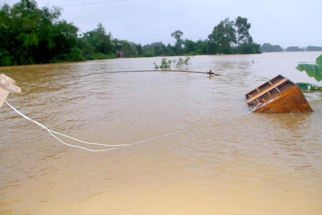 Nước cuốn trôi mất cái tủ gỗ, nhưng một hộ dân ở xã Lộc Yên (Hương Khê, Hà Tĩnh) đã may mắn neo tủ với cột gỗ để giữ cái tủ lại. Ảnh vnexpress.net