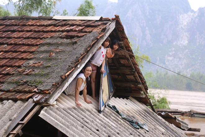 Tại huyện Tuyên Hóa (Quảng Bình) người dân lên nóc nhà để tránh lũ và liên lạc với bên ngoài. Ảnh vnexpress.net