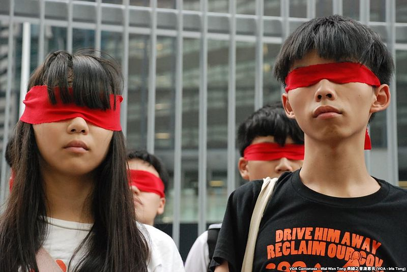 Trong buổi tuyên bố bãi khóa tháng 9/2014, Hoàng Chi Phong bịt mắt bằng khăn đỏ, tượng trưng cho chế độ đỏ của Trung Quốc làm mù mắt sinh viên. (Ảnh: VOA)