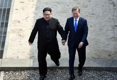 Ông Kim Jong Un và Moon Jae In nắm tay nhau bước qua dải phân cách biên giới Nam-Bắc Triều Tiên ngày 27/4/2018 (Ảnh: Press Pool)